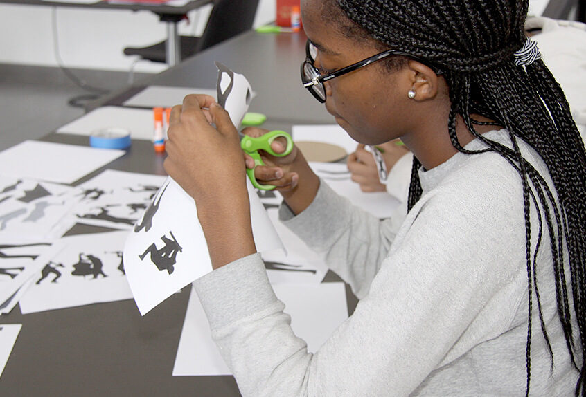 Middle School Harlem Renaissance art project student cutting figures from paper