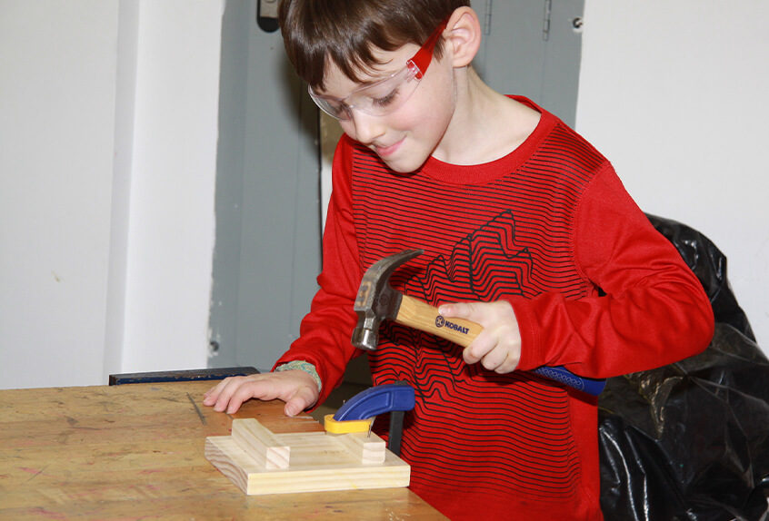 Lower school student learning to safely hammer nails