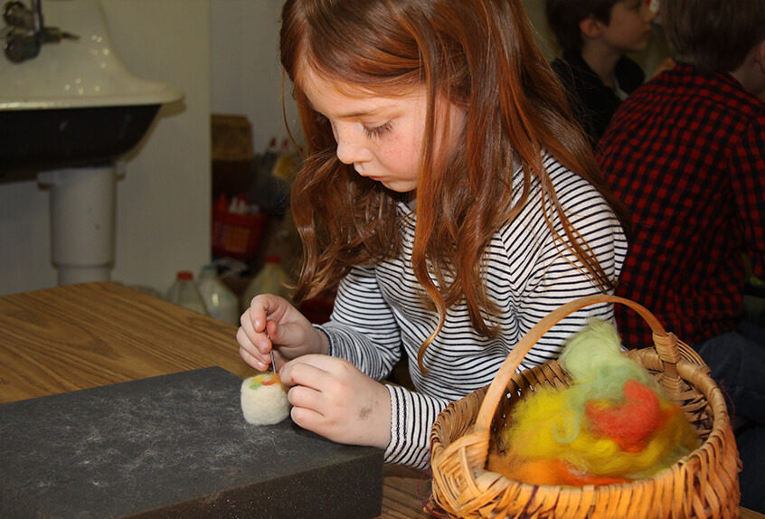 Lower school student learning about fiber arts