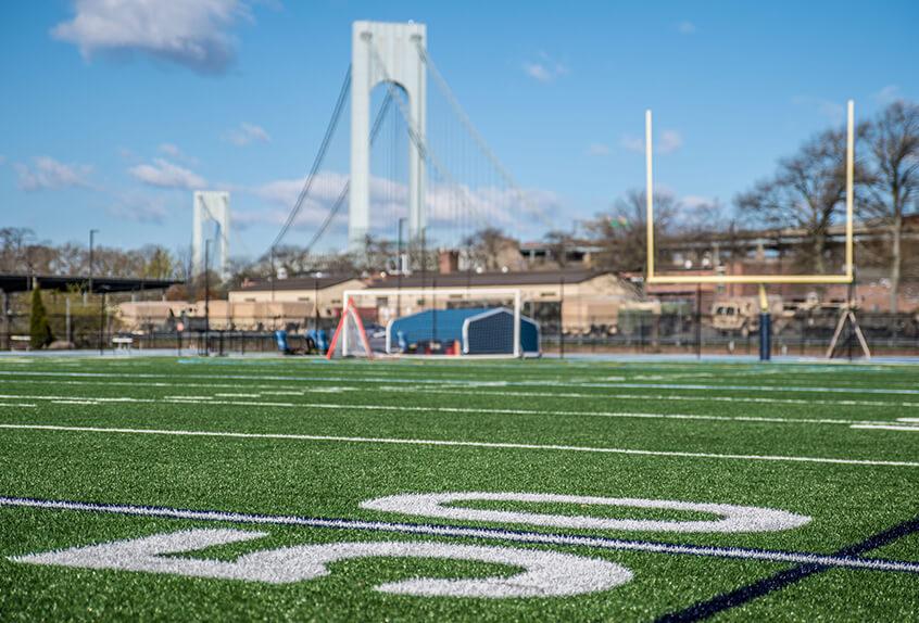 Football 50 yard line with bridge in backgroun