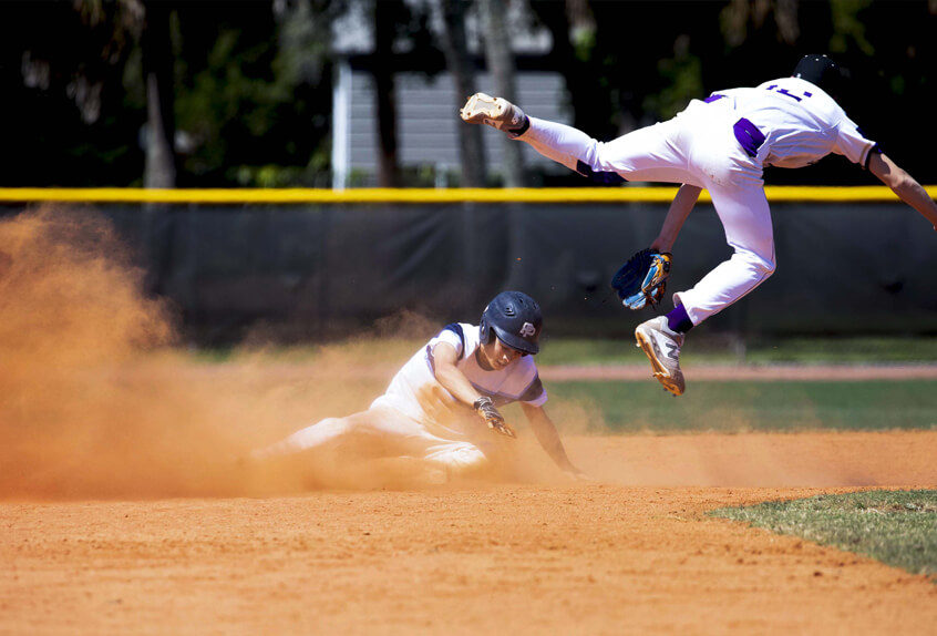 Poly Prep Baseball athlete sliding into base as the opposing team member leaps in the air for the ball