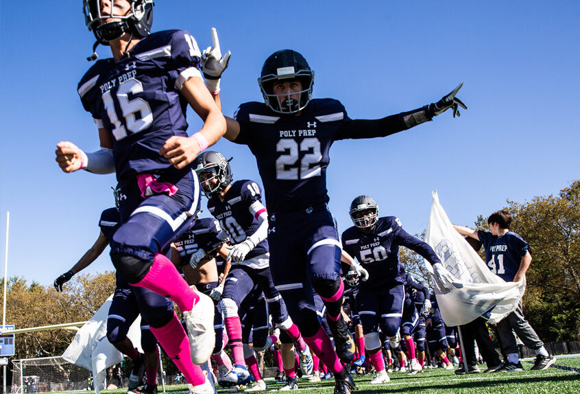Poly Prep Varsity Football Team breaking through a banner at the Homecoming game