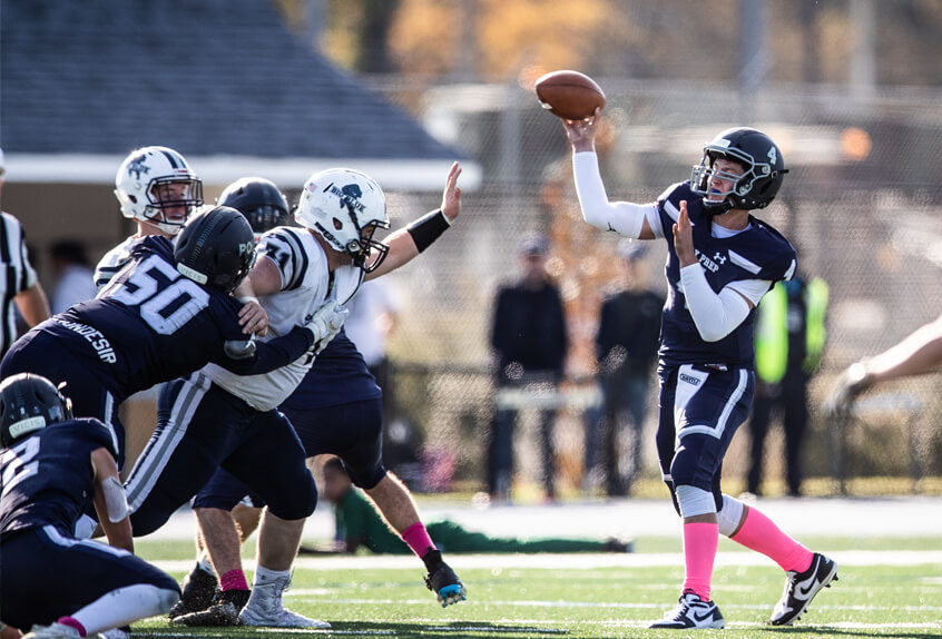 Poly Prep Varsity Football Quarterback throwing the ball as defense holds off the other team