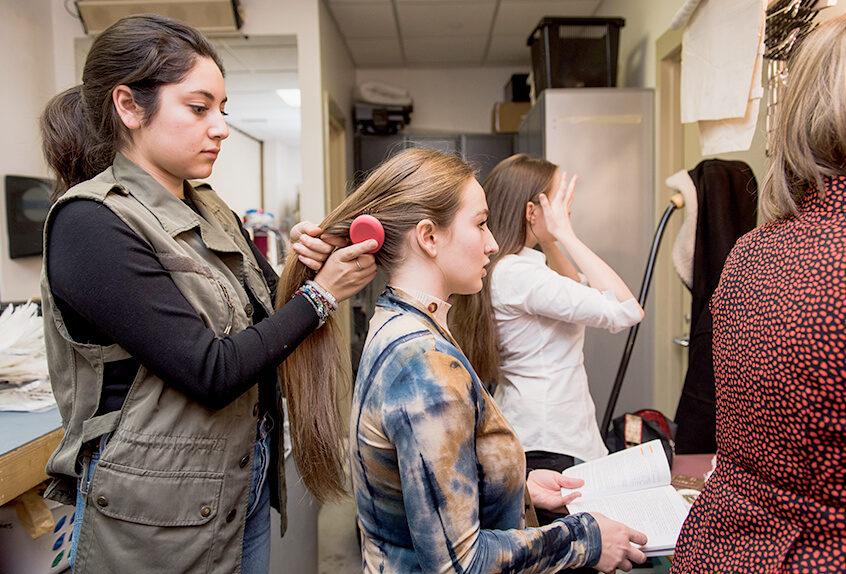 Alexandra Nava-Baltimore works backstage doing hair and makeup for performance.