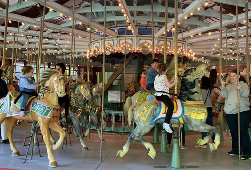 Lower school students riding on a carousel