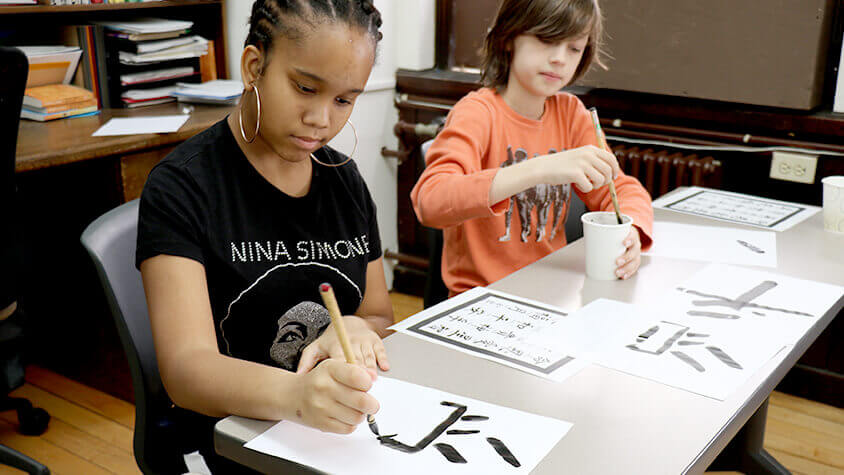 Middle school students doing calligraphy in mandarin