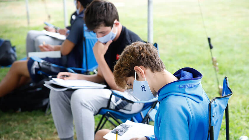 US Boys studying outdoors with masks